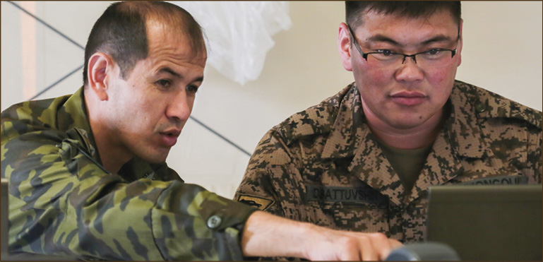 A Tajik National Army officer (left) and a Mongolian Army officer (right) evaluate a simulated event  during command post exercise Regional Cooperation 18 at Camp Edwards on Joint Base Cape Cod, Massachusetts, Sept. 15, 2018. Regional Cooperation is an annual exercise conducted by multiple national partners focusing on stability operations, border security and control, counter terrorism, counter narcotics,  and counter proliferation.